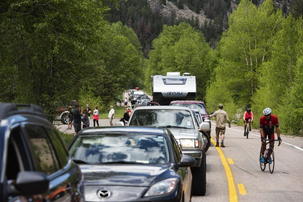 People mingle outside of their vehicles as they wait for the Independence Pass gate to be opened for the summer on Monday, June 1, 2020.