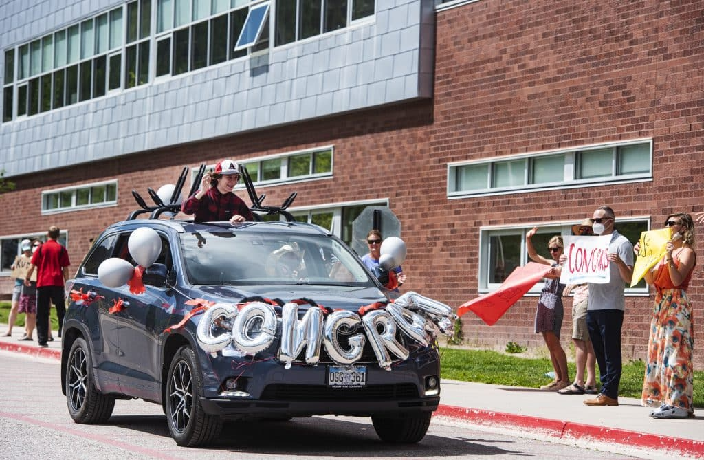 Eric Phillips, 14, rides with his head out of the sunroof of his family's car as his eighth grade teachers cheer him on during the Aspen Middle School continuation celebration for eighth graders on Thursday, June 4, 2020. (Kelsey Brunner/The Aspen Times)