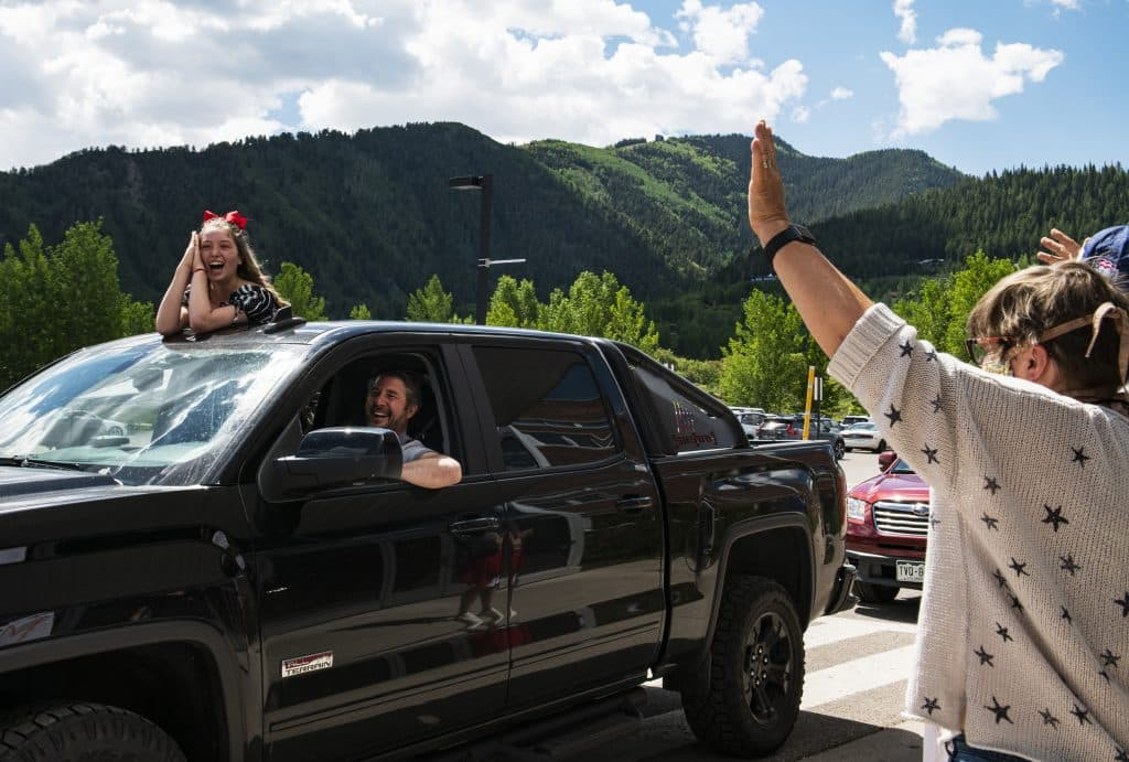 Gia Henrichon, 14, and her father Christian Henrichon enjoy the eighth grade continuation celebration as teachers cheer them through the drive-through event outside of Aspen Middle School on Thursday, June 4, 2020. Gia will be on the spirit and dance team at Aspen High School. (Kelsey Brunner/The Aspen Times)