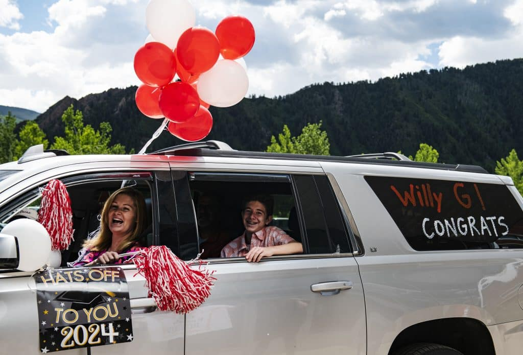 Maggie Gerardi, left, and Will Gerardi, 14, smile at teachers as Will is honored during the eighth grade continuation drive-through celebration outside of Aspen Middle School on Thursday, June 4, 2020. (Kelsey Brunner/The Aspen Times)