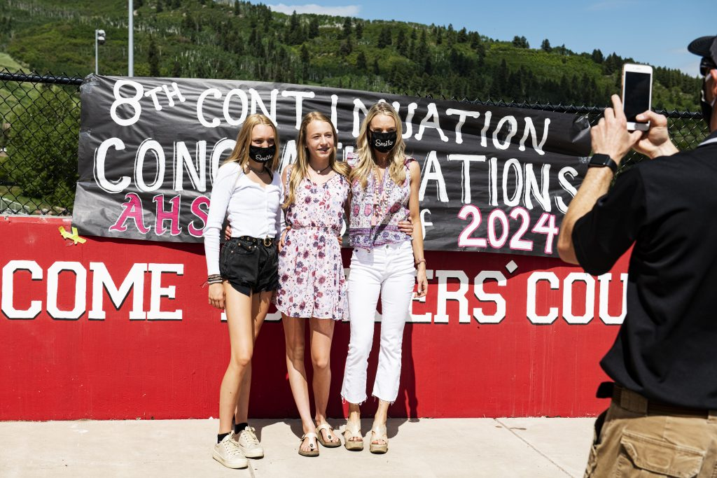 Lauren Haerter, left, Madelyn Haerter and Bethany Haerter pose for a photo in front of the banner next to Aspen Middle School during the eighth grade continuation celebration event on Thursday, June 4, 2020. (Kelsey Brunner/The Aspen Times)