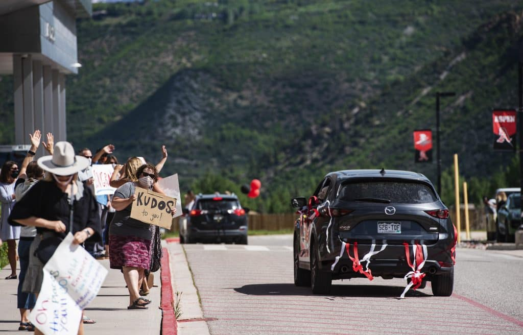 Aspen Middle School teachers cheer on their eighth grade students during a drive-through continuation celebration outside of the school on Thursday, June 4, 2020. (Kelsey Brunner/The Aspen Times)