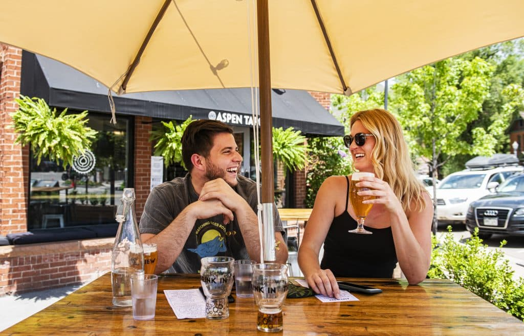 Blake Migliara, left, and Lauren West drink Aspen Tap beers on the patio of the restaurant in Aspen on Tuesday, June 2, 2020. The two drove over Independence Pass from Twin Lakes for the day.