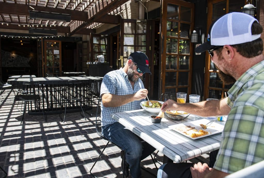 Seth Hmielowski, left, and Brent Tardie have lunch on the patio of Mi Chola on Tuesday, June 2, 2020.