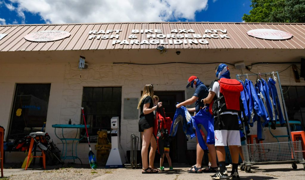 A group of rafters try on dry suits and life jackets at Glenwood Adventure Company on Tuesday afternoon.
