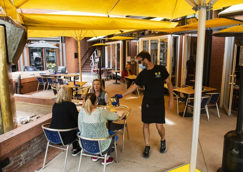 A waiter at Mezzaluna refills water for customers dining on the patio in Aspen.