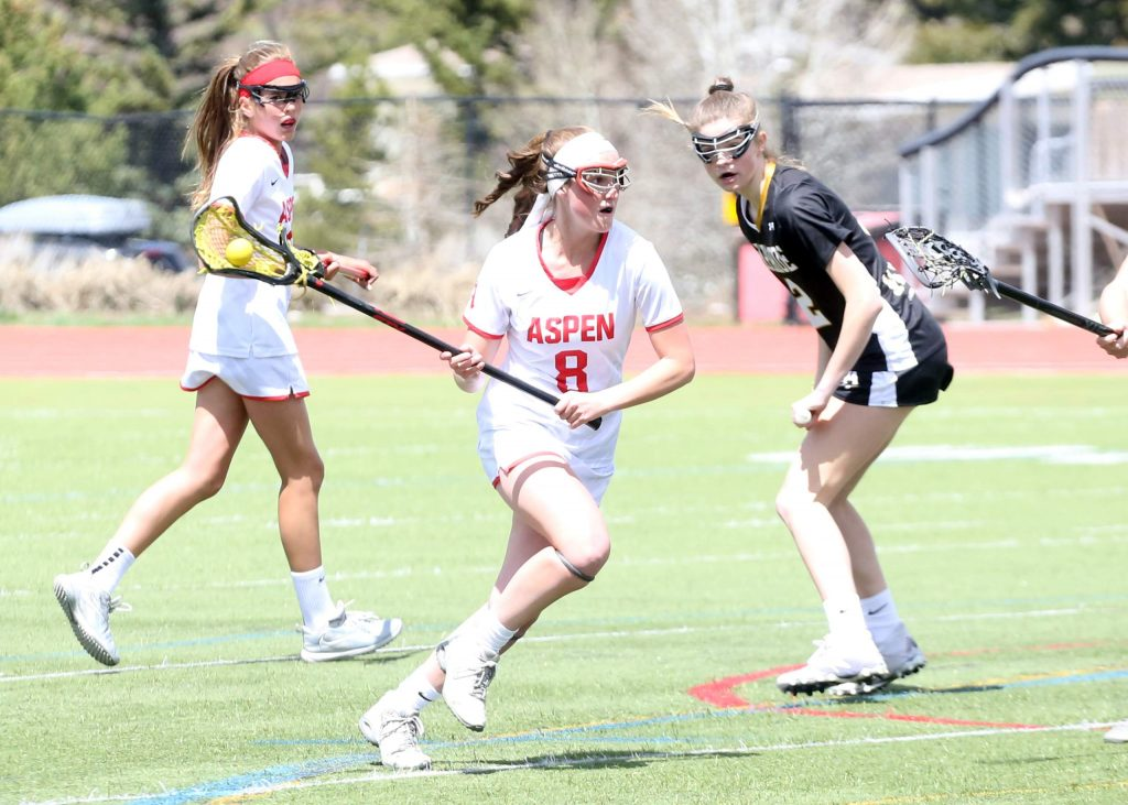 Aspen High School's Charlotte Howie brings the ball upfield in a girls lacrosse game against Arapahoe on Saturday, April 27, 2019, on the AHS turf. (Photo by Austin Colbert/The Aspen Times).