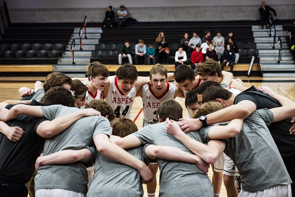 Aidan Ledingham (44) huddles up with the varsity boys basketball team before the the tip off of the playoff game against Cedaredge High School on Saturday, Feb. 22, 2020. (Kelsey Brunner/The Aspen Times)