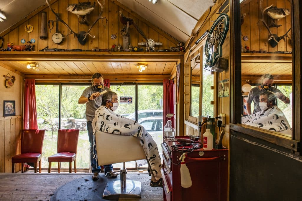 Chad Bones gives Larry Mills a haircut at the Basalt Barber Shop a week after they reopened on Tuesday, May 12, 2020. Garfield County began relieving COVID-19 restrictions on the first of May, but Lonnie Bones said they waited a little longer to reopen the shop.