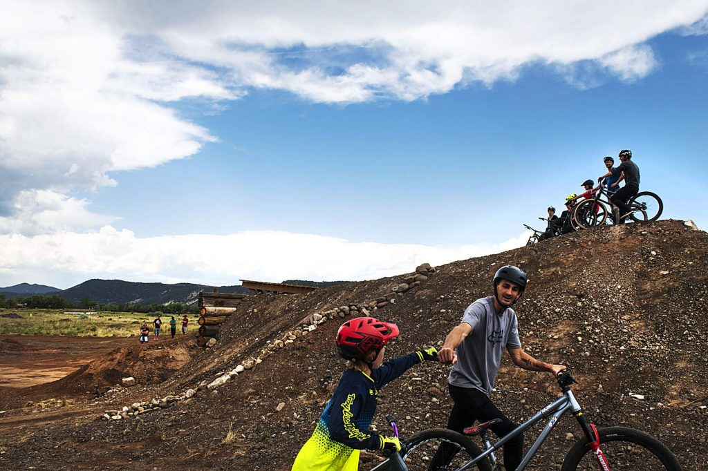DJ Brandt fist bumps another biker as they walk back to the drop in point in one area of the new bike park in Crown Mountain Park on Thursday, June 25, 2020.