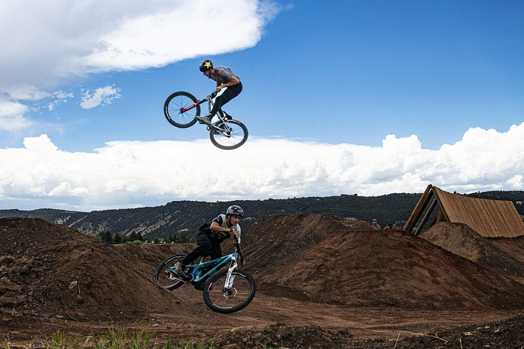 DJ Brandt jumps over Reed Boggs in the new bike park at Crown Mountain Park on Thursday, June 25, 2020.
