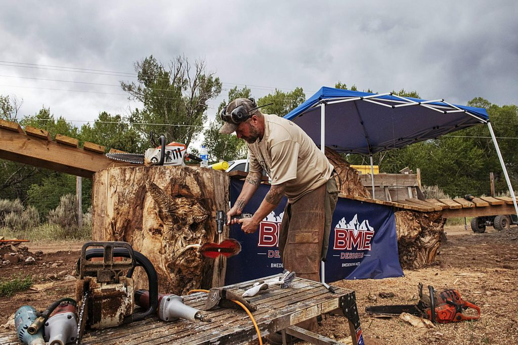 A chainsaw artist carves into a tree stump in the enchanted forest section of the new bike park in Crown Mountain Park on Thursday, June 25, 2020. The enchanted forest is made up of a boardwalk feature and found wood.