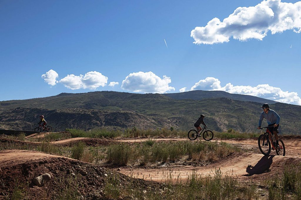 A family utilizes a dirt track at the bike park in Crown Mountain Park on Tuesday, June 23, 2020.