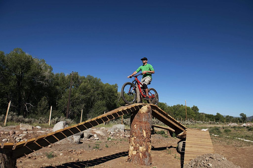 Crown Mountain Park manager Nate Grinzinger sits on top of the boardwalk in the enchanted forest section of the bike park in Crown Mountain Park on Tuesday, June 23, 2020.