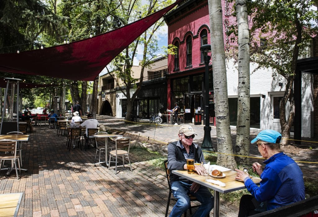 """Warwick Ford, center left, and Nola Ford share a lunch in the outdoor seating at Red Onion in downtown Aspen on Tuesday, May 26, 2020. """"It's wonderful, it's our first day back at Red Onion,"""" said Nola. """"We're locals and we love it!"""""""