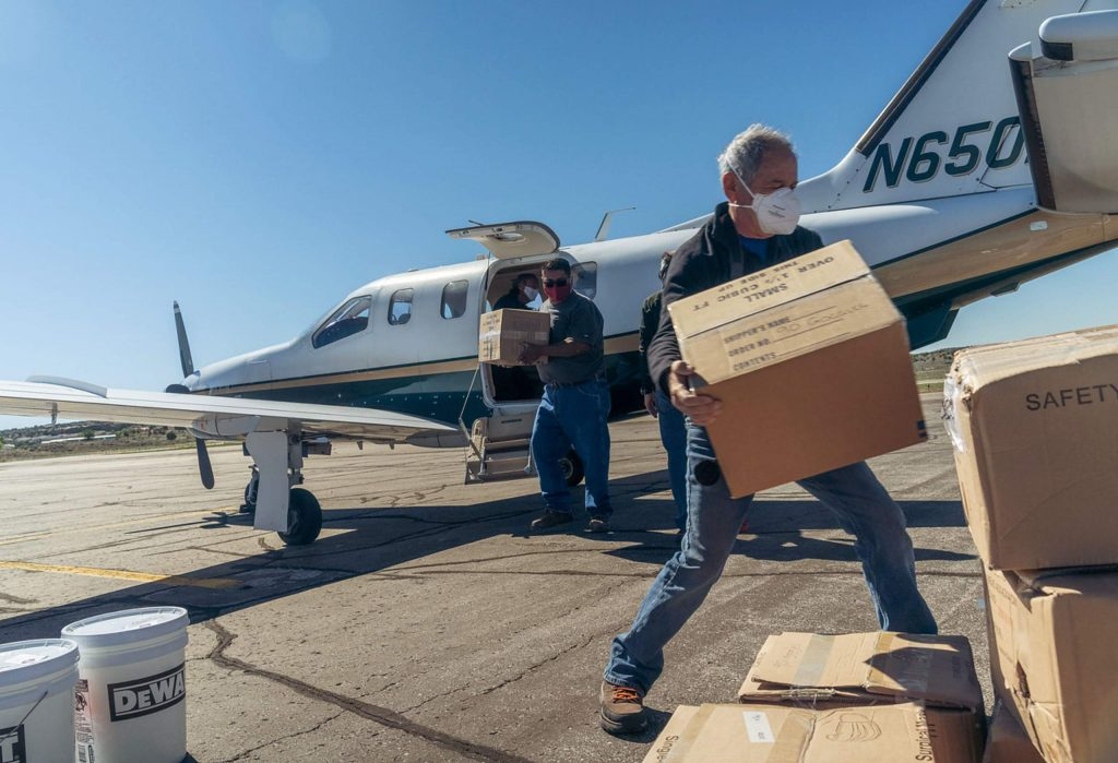 Bruce Gordon of EcoFLight, right, and Darren Sanchez of the Zuni tribe unload PPE from Mike Waters' airplane delivering protective equipment from Aspen.