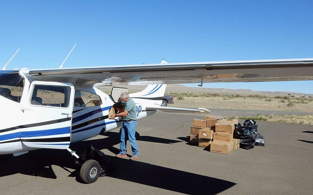 Mike Taets unloads masks, face shields and sanitizer from his airplane Wednesday after flying from Aspen to the Hopi Reservation in northeastern Arizona.