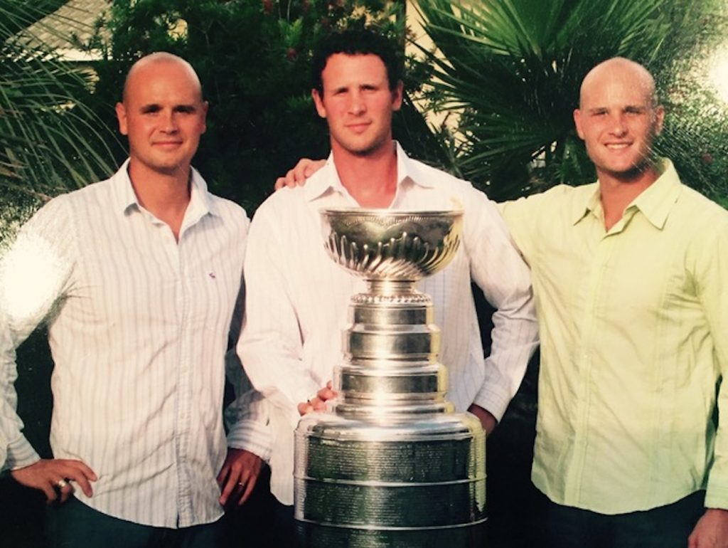 From left, brothers Jasen, Nolan and Harlan Pratt pose with the Stanley Cup trophy. Nolan won the Stanley Cup as a player with both the Colorado Avalanche and Tampa Bay Lightning, and currently is an assistant coach with the Avalanche.