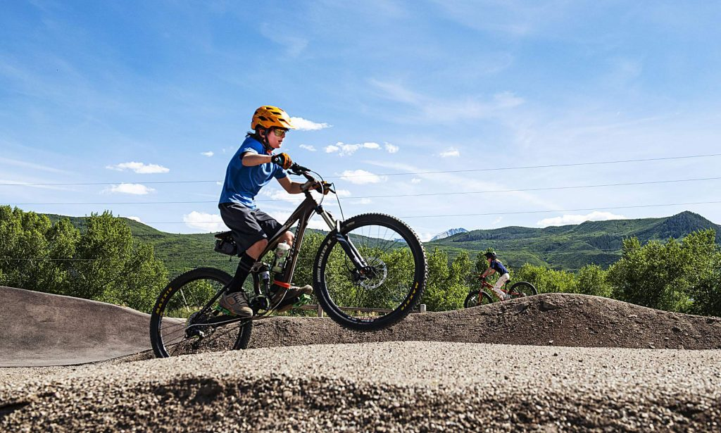 Anderson Tippet, 8, left, and Ellis Burggraf, 7, race around the Crown Mountain Park bike park in El Jebel on Tuesday, June 2, 2020. This was Ellis' third time at the bike park. Their parents said they were trying to find new things fro the kids to do, so they started coming here this season. Tippet and Burggraf met in preschool and have been close friends since. (Kelsey Brunner/The Aspen Times)