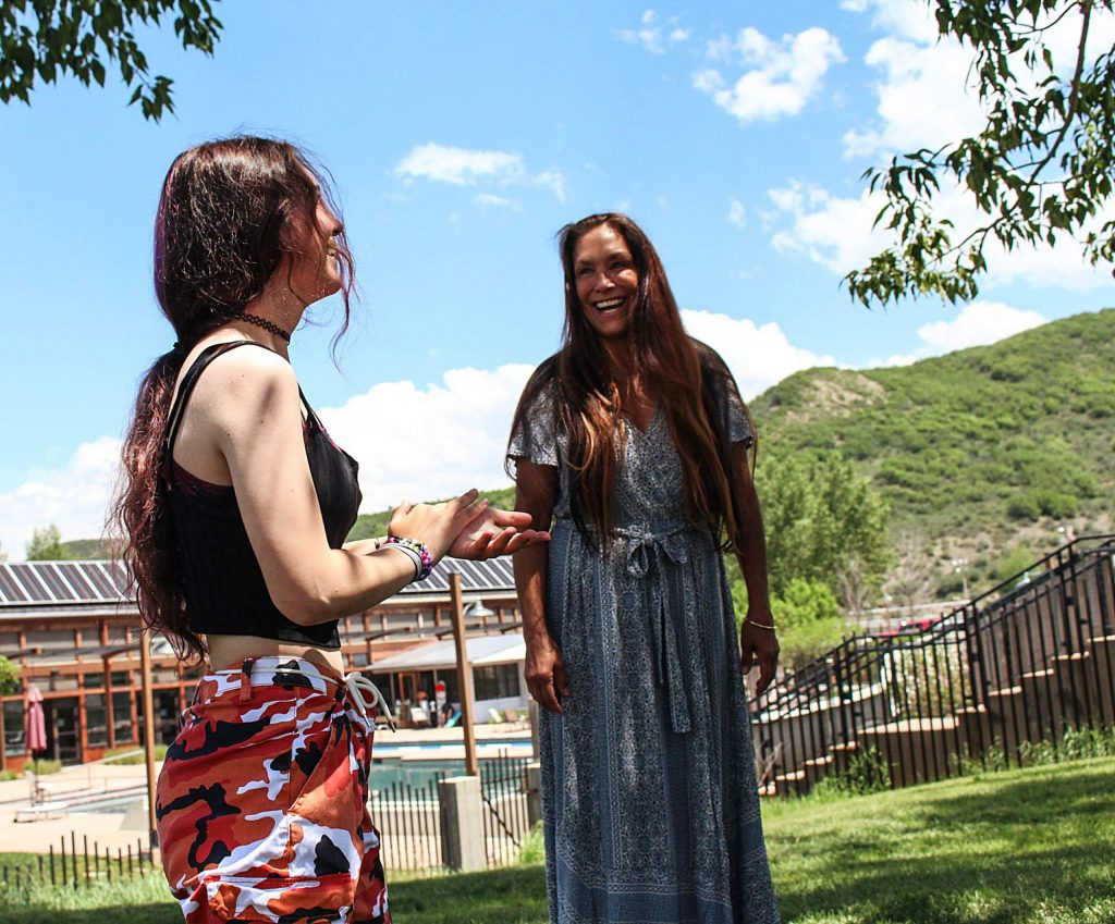 Michelle McCuiston and her daughter, Jasmine, laugh as she jumps down from a tree in Snowmass Town Park on June 18, 2020. (Maddie Vincent/Snowmass Sun).