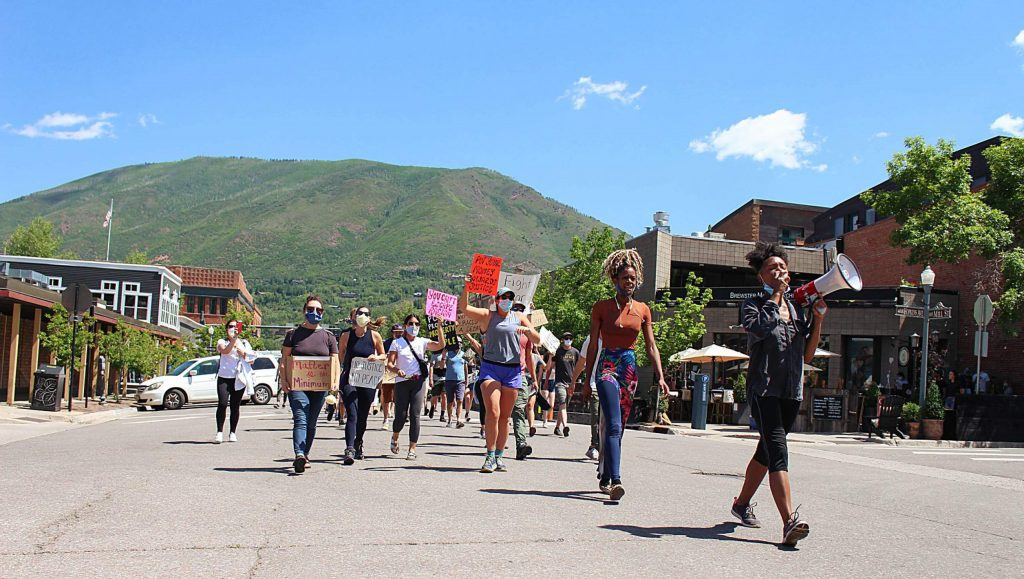 Jenelle Figgins, right, and Sajari Simmons, second from right, lead dozens of people down Mill Street during the Black Lives Matter rally in Aspen on June 14, 2020