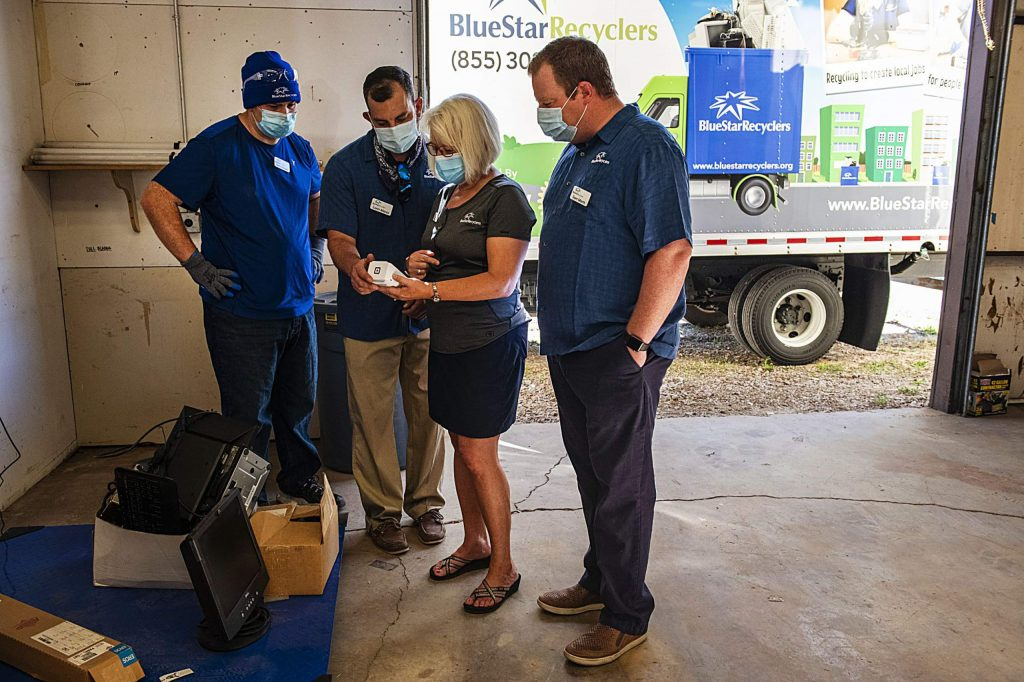 Blue Star Recyclers' Danny Hennessy, left, Lorin Marco, Janet Morris, and Sam Morris weigh the first material dropped off at the Roaring Fork Valley Mountain Recycling Operations grand opening in Basalt on Wednesday, June 24, 2020. (Kelsey Brunner/The Aspen Times)