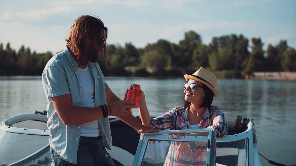 Young couple toasting each other with cans of beer as they relax in the evening on a lake in a motorboat while enjoying their summer vacation.