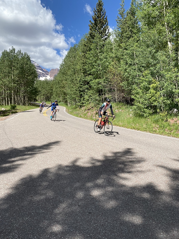 Chris Davenport smiles at the front of the pack, descending Maroon Creek Road from the Bells.
