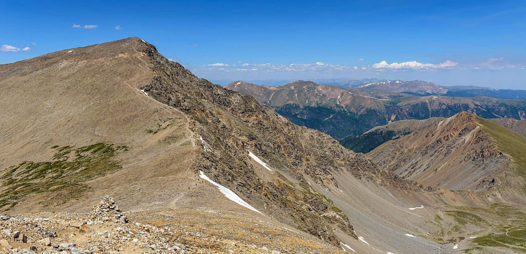 A summer panoramic view of steep south slopes of Torreys Peak (14,267 ft), seen from summit of Grays Peak (14,270 ft), Colorado, USA.