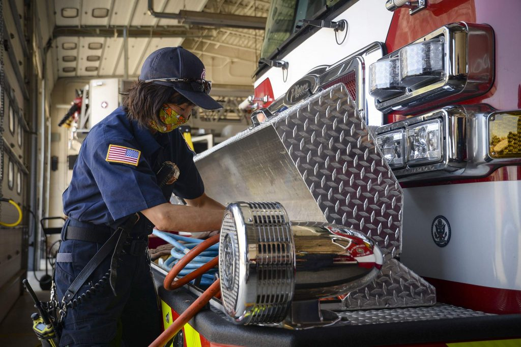 CRFR firefighter Rie Pruitt roles up a hose during her shift Tuesday at Station 43 in Rifle. Colorado River Fire Rescue announced they will be reducing services and combining staff as they make budget cut through the end of the year.