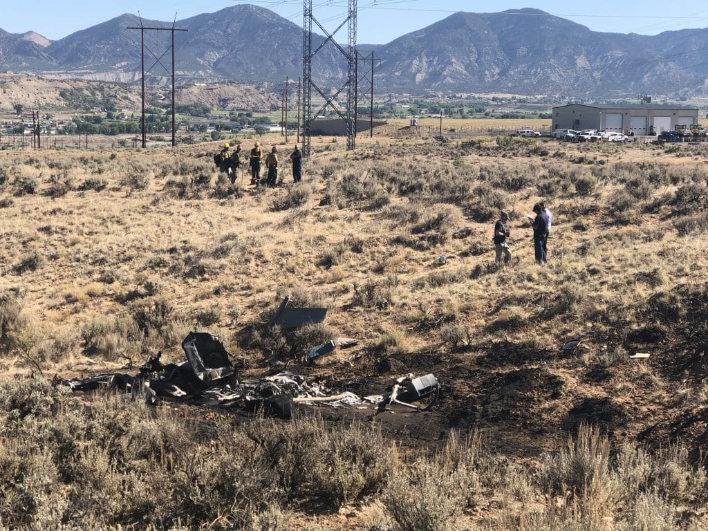 Emergency officials inspect the scene of a helicopter crash south of Rifle Saturday morning. Two men were taken to an area hospital.