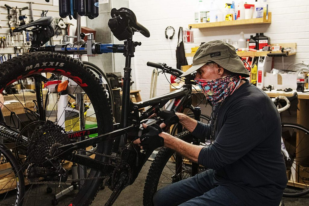 Patrick Dietz, owner of Aspen Bicycles, puts an auxiliary battery on his personal electric mountain bike in his shop on Friday, July 17, 2020.