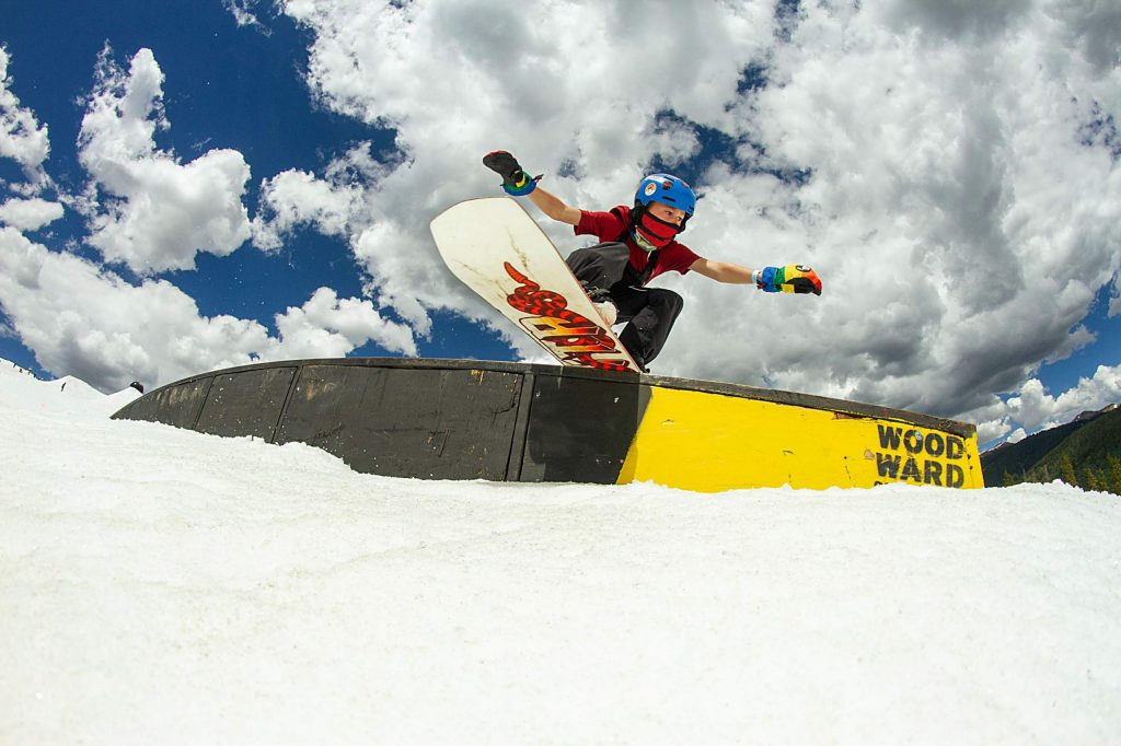 A young snowboarder rides a rainbow rail in the Woodward Copper Central Park terrain park at Copper Mountain Resort.