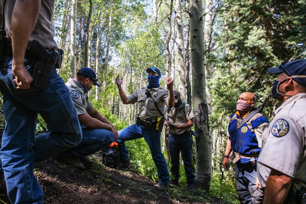 Colorado Parks and Wildlife officers debrief after successfully tracking and euthanizing a bear at an abandoned mine on Aspen Mountain, Friday, July 10, 2020. The euthanized bear was suspected of attacking an Aspen man early on Friday morning.