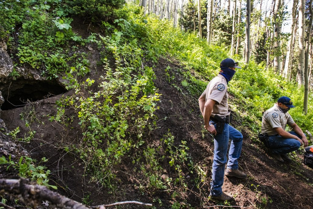 Colorado Parks and Wildlife officers stand next to the abandoned mine where a bear was tracked and euthanized on Aspen Mountain, Friday, July 10, 2020. The euthanized bear was suspected of attacking an Aspen man early on Friday morning.