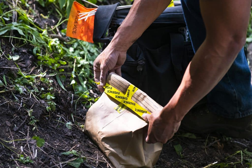 An evidence bag is sealed before being packed out from near an abandoned mine on Aspen Mountain, Friday, July 10, 2020. A bear suspected of attacking an Aspen man early on Friday morning was tracked to the mine and euthanized by Colorado Parks and Wildlife officers.