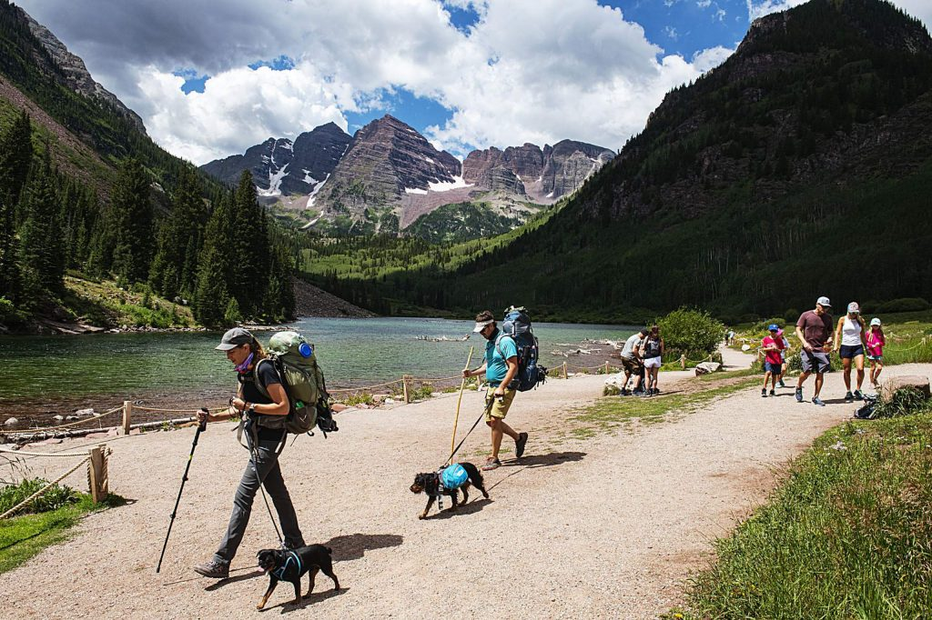 People walk by Maroon Lake in view of the Maroon Bells on Wednesday, July 29, 2020. This season, the U.S. Forest Service implemented a reservation system to limit the amount of people visiting the scenic area. (Kelsey Brunner/The Aspen Times)