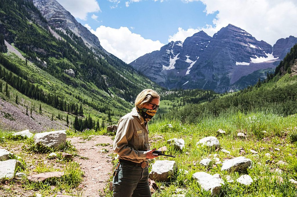 U.S. Forest Service's Katy Nelson uses her radio at the Maroon Bells amphitheater on Wednesday, July 29, 2020. (Kelsey Brunner/The Aspen Times)