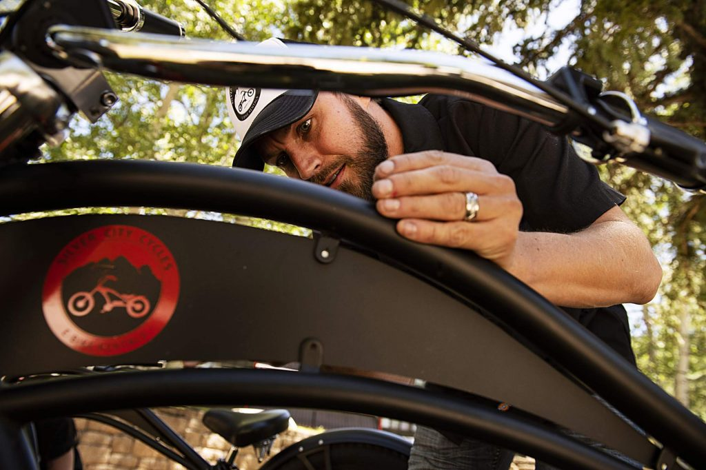 Derek Attema puts a Silver City Cycles flag on one of the rental e-bikes in Aspen on Wednesday, July 1, 2020. (Kelsey Brunner/The Aspen Times)