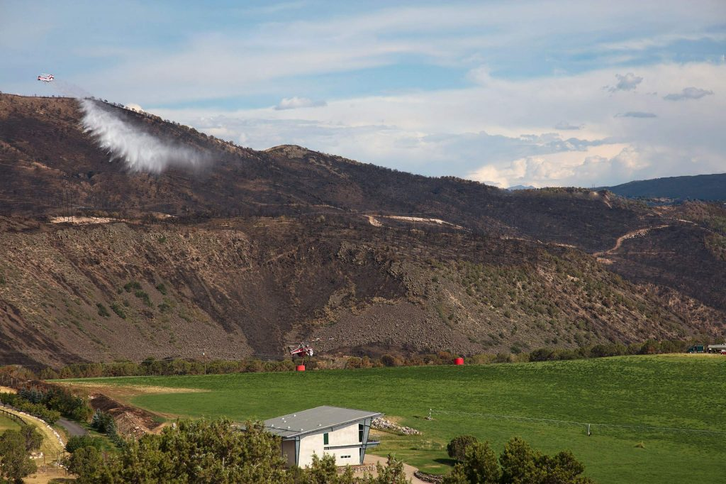 One helicopter lands to pick up fire retardant on the Kim family ranch while another delivers its payload on Basalt Mountain in July 2018.