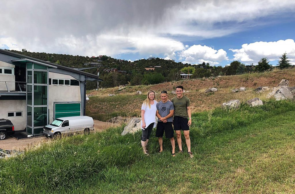 Laura, Alex and Tai Kim stand outside their home in Missouri Heights on Monday, July 6. Two years ago the Lake Christine Fire topped the berm behind them and came within yards of their home.
