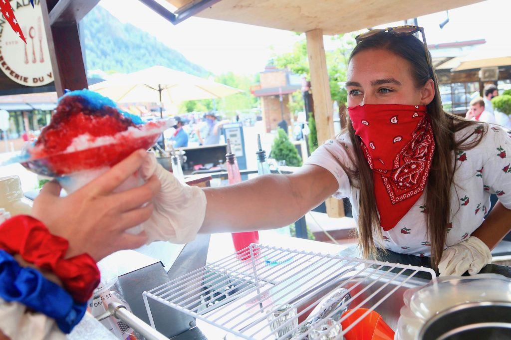 Nikki Hausherr serves a customer at the Snowy Pineapple shaved ice stand in front of Radio Boardshop on Saturday, July 4, 2020, in downtown Aspen. (Photo by Austin Colbert/The Aspen Times)