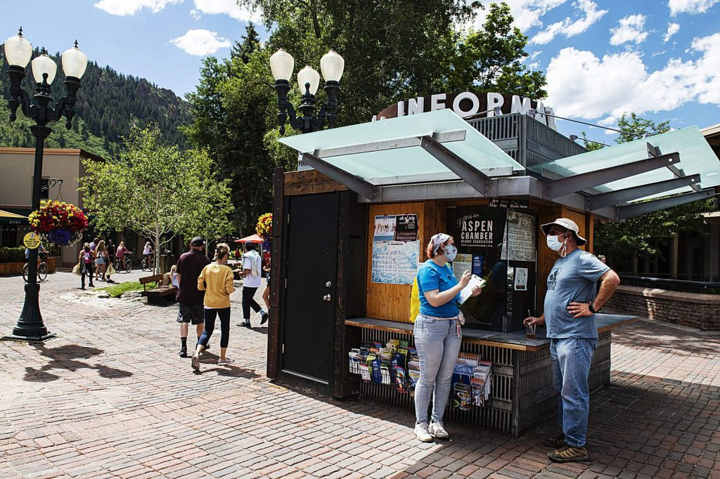 Street ambassador Chey French talks to visitors near the information kiosk while handing out a bag from the Aspen Chamber Resort Association's containing a mask, sticker and safety information in downtown Aspen on Thursday, July 2, 2020. (Kelsey Brunner/The Aspen Times)