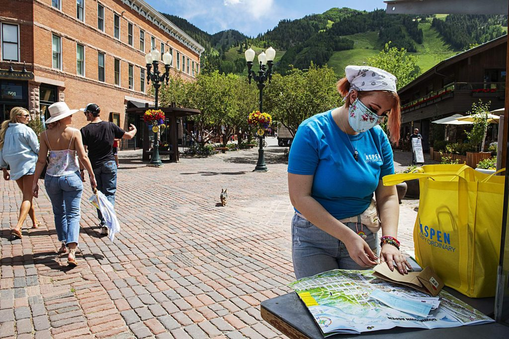 Street ambassador Chey French lays out the contents of the Aspen Chamber Resort Association's bag that contains a mask, sticker and safety information in downtown Aspen on Thursday, July 2, 2020. (Kelsey Brunner/The Aspen Times)
