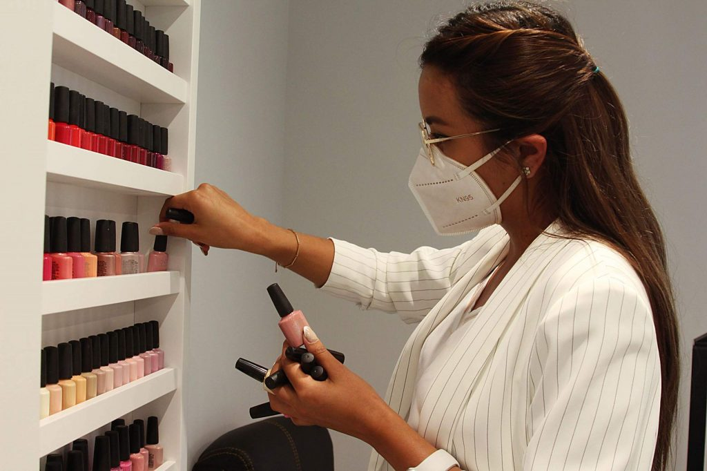 Brenda Monrroy, a receptionist at Alux Spalon, organizes nail polish in the salon's new Snowmass Base Village location on July 7, 2020. (Maddie Vincent/Snowmass Sun).