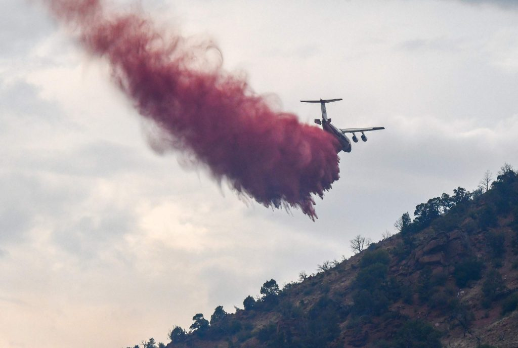 An airtanker drops fire retardant on the hillside after a fire broke out above I-70 at MM 113 in South Canyon