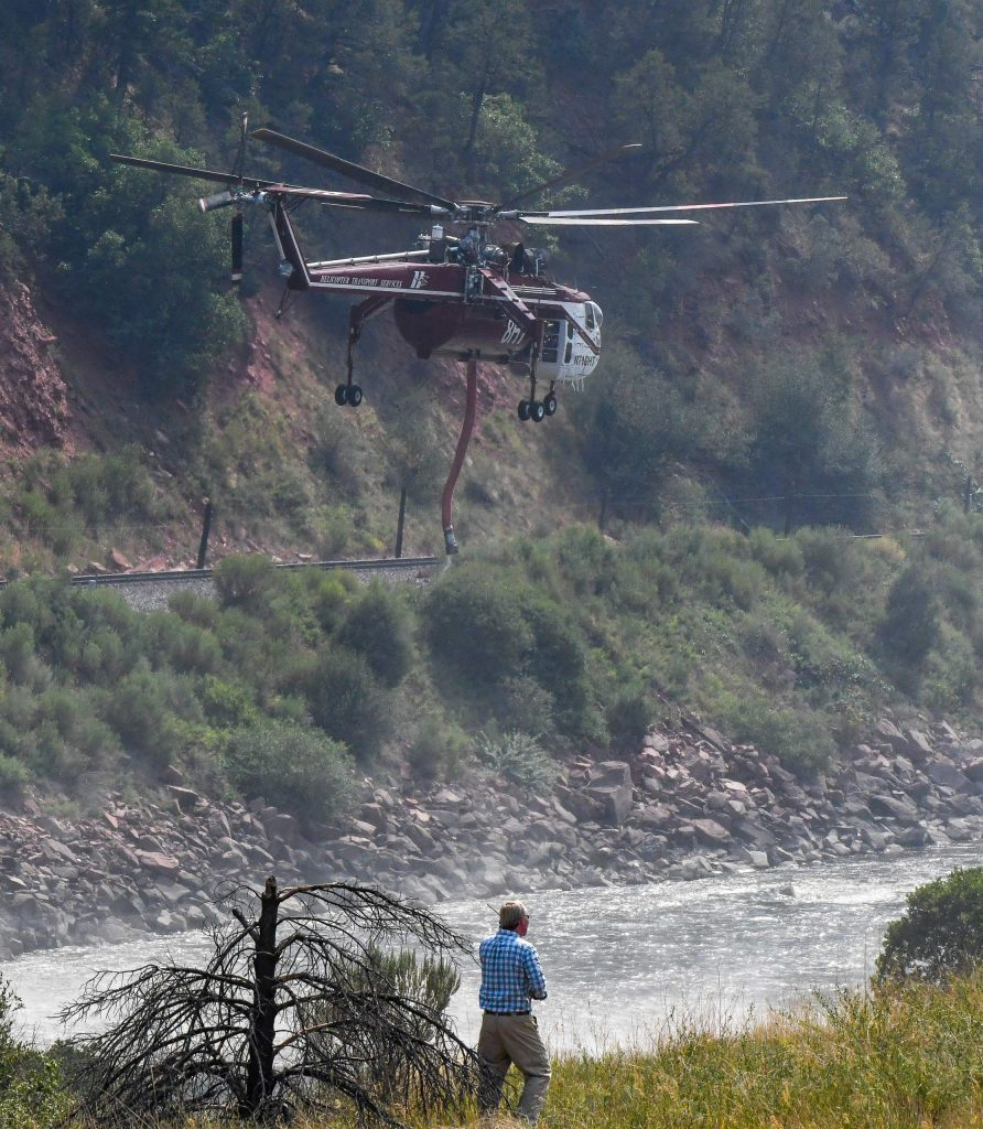 A man watches as a type I fire helicopter heads back to take water from the Colorado River after a fire broke out on the hillside of I-70 at MM 113 in South Canyon
