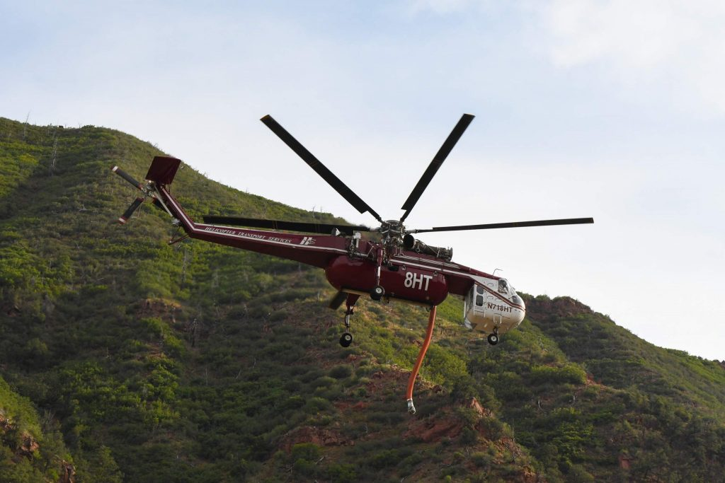 A type I fire helicopter heads back to take water from the Colorado River after a fire broke out on the hillside of I-70 at MM 113 in South Canyon.