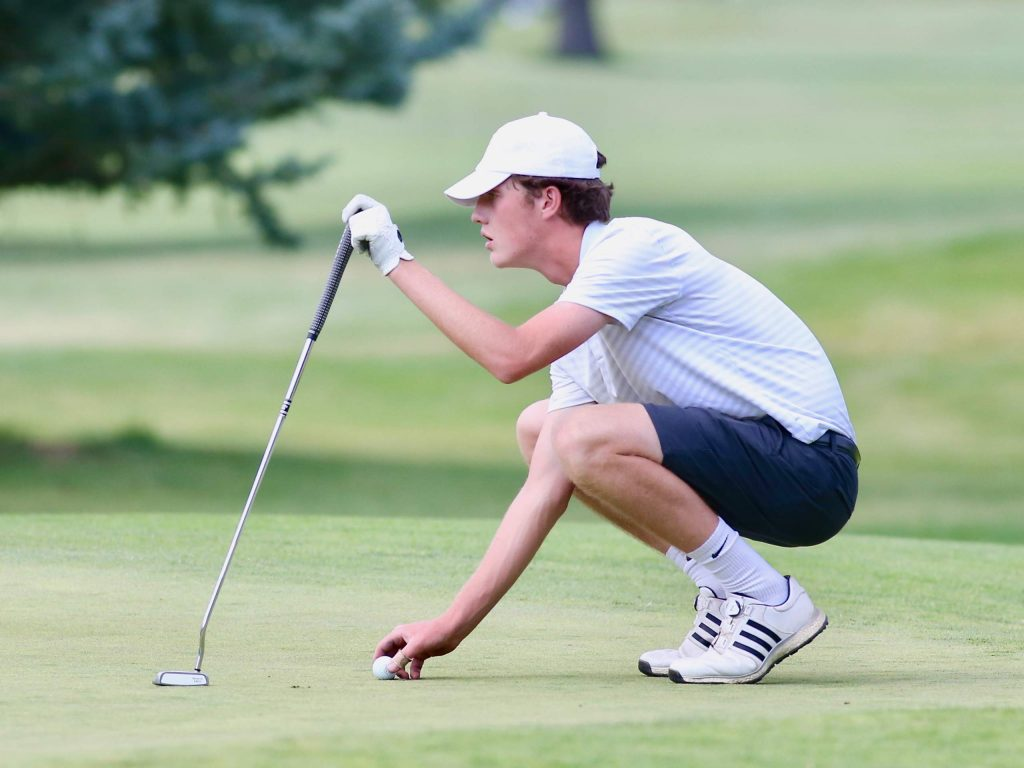 Keaton Miller lines up a putt during Aspen High School boys golf tryouts on Tuesday, Aug. 4, 2020, at Aspen Golf Club. (Photo by Austin Colbert/The Aspen Times)