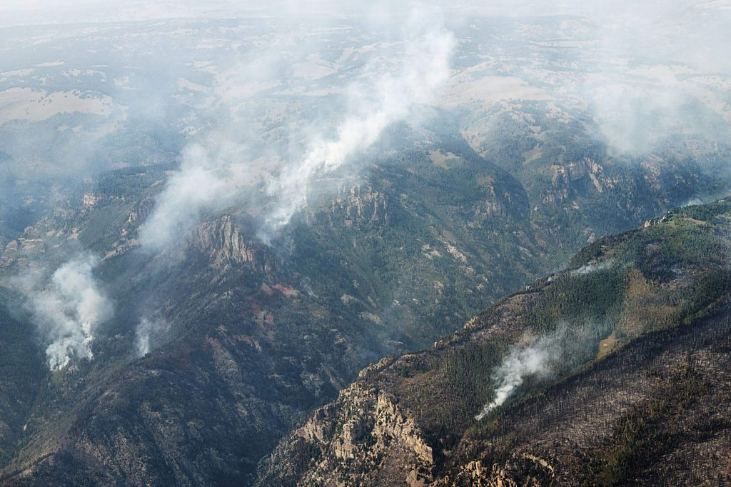 Smoke from the Grizzly Creek Fire dots the ridge line on Monday, August 24, 2020.